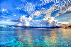 Bright blue water and light cloudy sky at one of the Maldives islands.